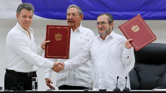 President Juan Manuel Santos, left, and  FARC official Timoleon Jimenez  mark a ceasefire in June.