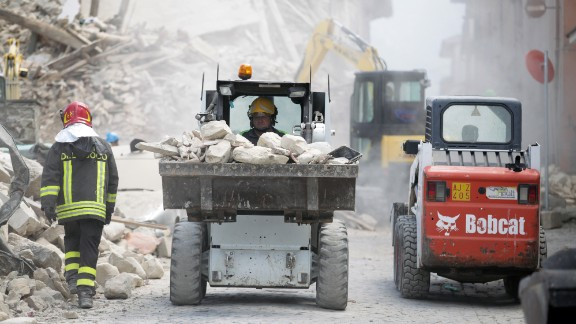 A rescue worker drives a truck of rubble as cleanup operations begin in Amatrice.