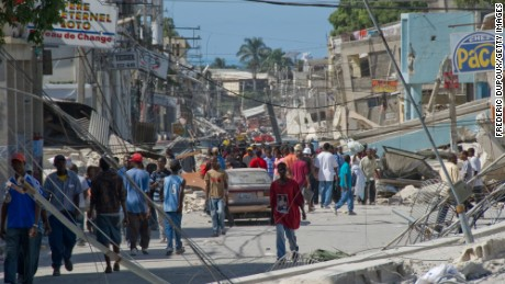 People wander the streets in front of the remains of a boarding school in the downtown area January 13, 2010 in Port-au-Prince, Haiti.