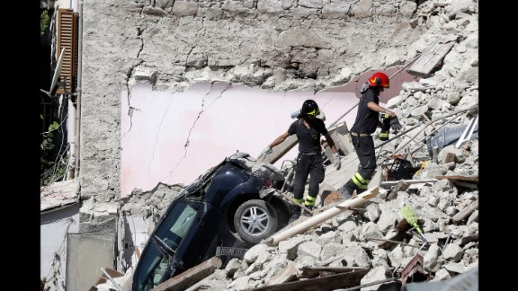 Rescuers make their way through destroyed houses in Pescara del Tronto on Thursday, August 25. It
