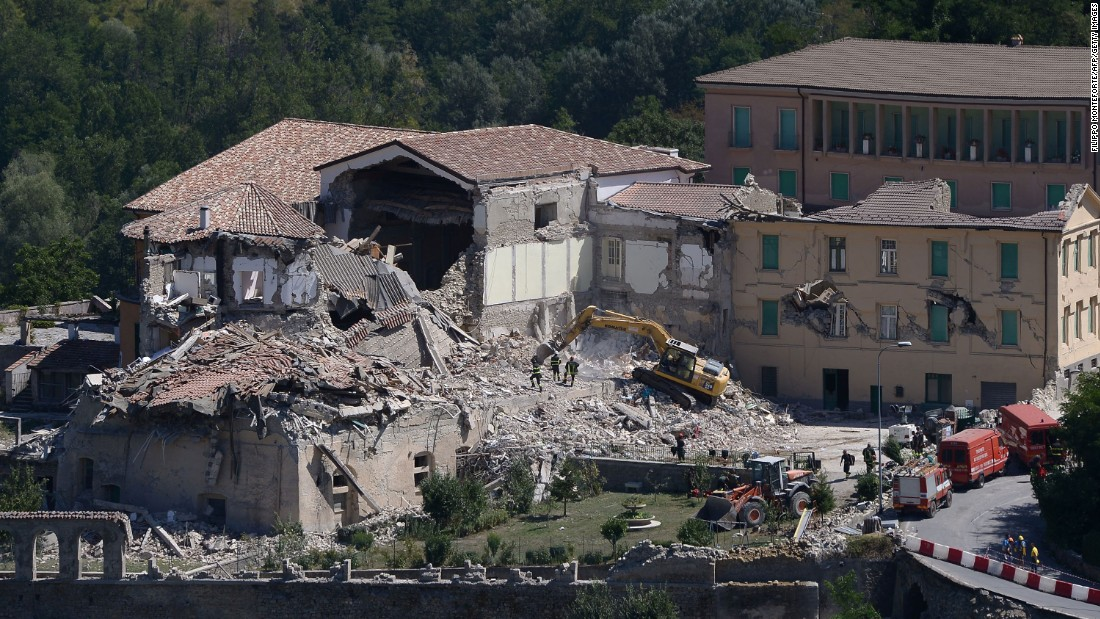 Rescue and emergency service personnel use an excavator to search for victims under the remains of a building in Amatrice on August 25.