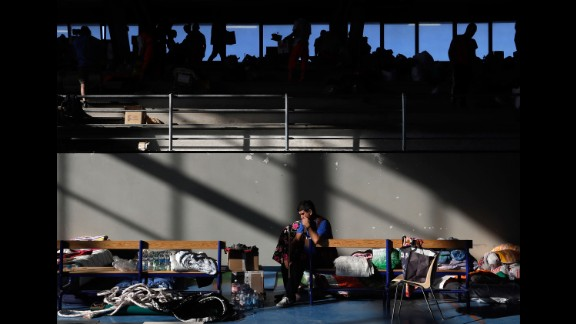 A man rests on a bench after spending the night in a makeshift camp set up inside a gym in Amatrice on August 25.