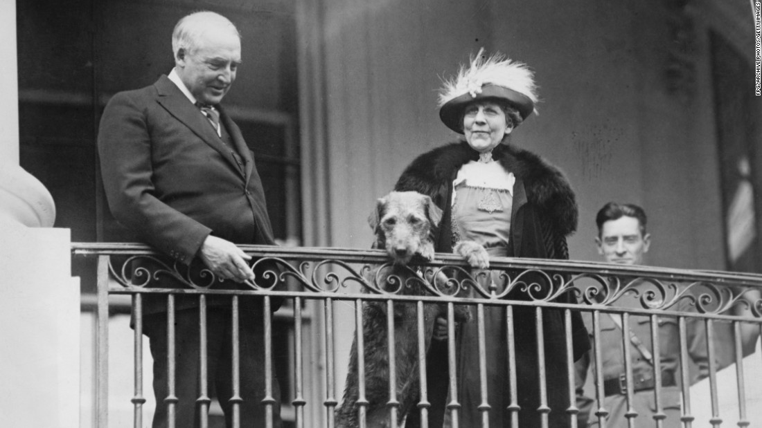 President Warren G. Harding, first lady Florence Harding and their Airedale terrier, Laddie Boy, watch from a balcony as the annual Easter Egg Roll takes place on the White House lawn, circa 1922.