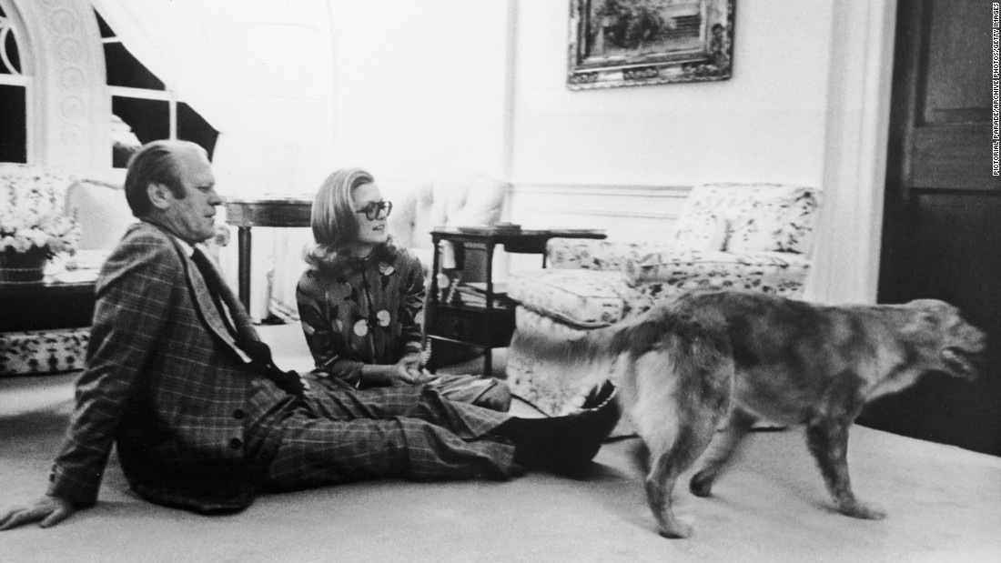 President Gerald Ford sits with his daughter, Susan, on the floor of the White House's Great Hall watching their golden retriever, Liberty, circa 1978.