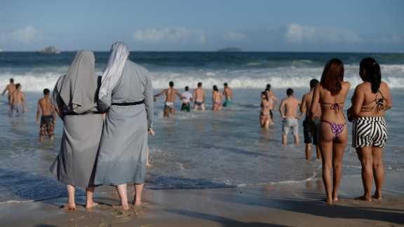"Two Polish nuns look at people bathing as hundreds of thousands of young Catholic pilgrims attending World Youth Day (WYD) start gathering at Copacabana beach in Rio de Janeiro for a prayer vigil with Pope Francis, on July 27, 2013. In a speech to Brazil's political, religious and civil society leaders earlier, Pope Francis said a ""constructive dialogue"" was needed to confront the country's social turmoil, referring to the massive street protests that rocked Brazil last month to demand an end to corruption and better public services.  AFP PHOTO / YASUYOSHI CHIBA        (Photo credit should read YASUYOSHI CHIBA/AFP/Getty Images)"
