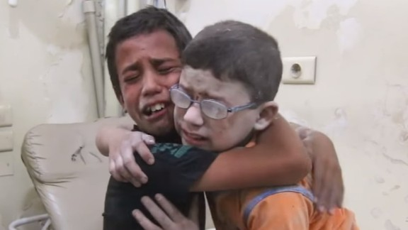 A harrowing video shows two boys crying and wrapping their arms around each other after a barrel bomb killed at least 13 people in Aleppo.