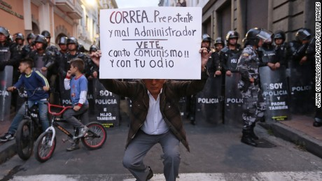 "A man holds a sign reading ""Correa...arrogant and bad administrator. Go away with your communism and your hatred"", referring to Ecuadorean President Rafael Correa, in from of a line of riot policemen during a march called by the Ecuadorean National Union of Educators (UNE) against the government in downtown Quito on August 25, 2016.  / AFP / JUAN CEVALLOS        (Photo credit should read JUAN CEVALLOS/AFP/Getty Images)"