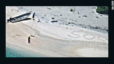 Two stranded mariners were rescued after a US Navy aircraft crew spotted SOS etched into the sand while flying over a deserted beach in Micronesia.