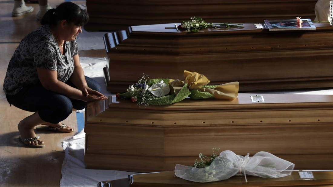 A woman touches a coffin of one of the victims during the funeral.