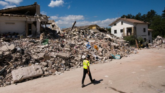 An emergency responder passes by the rubble of the building in Amatrice where Roberto Partenza and his family lived before the earthquake struck in the pre-dawn hours of Wednesday, August 24.