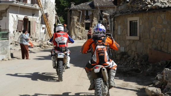 Volunteers on motorbikes drive through the town of Villa San Lorenzo a Flaviano, Italy, on August 28 as they bring supplies to smaller villages.