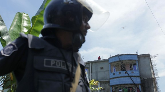 Bangladesh police stand guard near the building that was raided.