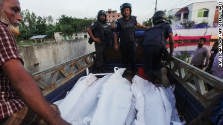 Bangladesh policemen transport the bodies of suspected militants involved with the Dhaka cafe attack following an operation to storm a militant hideout in Narayanganj, south of Dhaka on August 27, 2016.