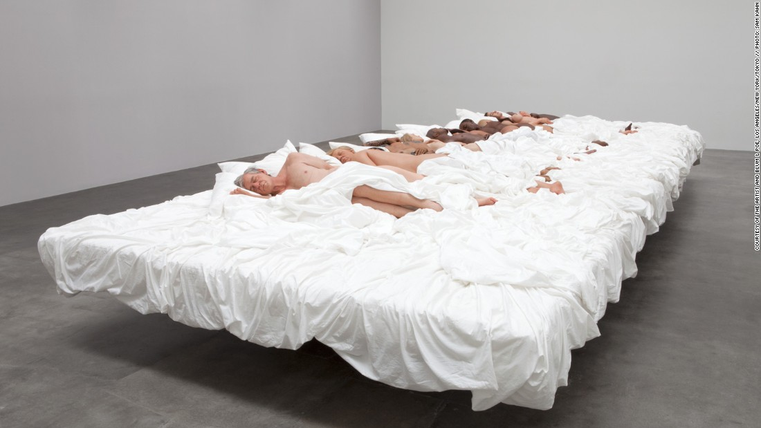 The video featured a large bed with lifelike sculptures that depict major cultural icons.