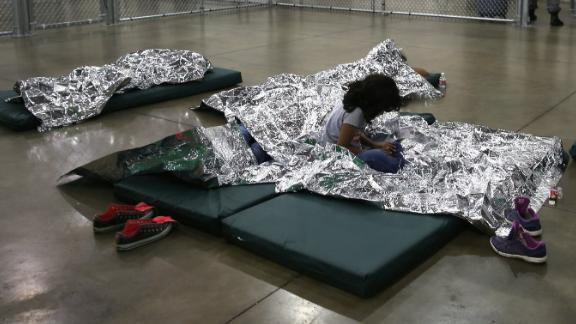 A girl from Central America rests on thermal blankets at a detention facility run by the U.S. Border Patrol on September 8, 2014 in McAllen, Texas. The Border Patrol opened the holding center to temporarily house the children after tens of thousands of families and unaccompanied minors from Central America crossed the border illegally into the United States during the spring and summer. Although the flow of underage immigrants has since slowed greatly, thousands of them are now housed in centers around the United States as immigration courts process their cases.