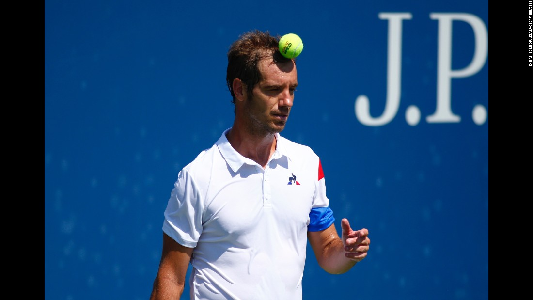 Tennis player Richard Gasquet plays with the ball during a first-round U.S. Open match on Monday, August 29. Gasquet, the tournament's 13th seed, was upset by Kyle Edmund in straight sets.