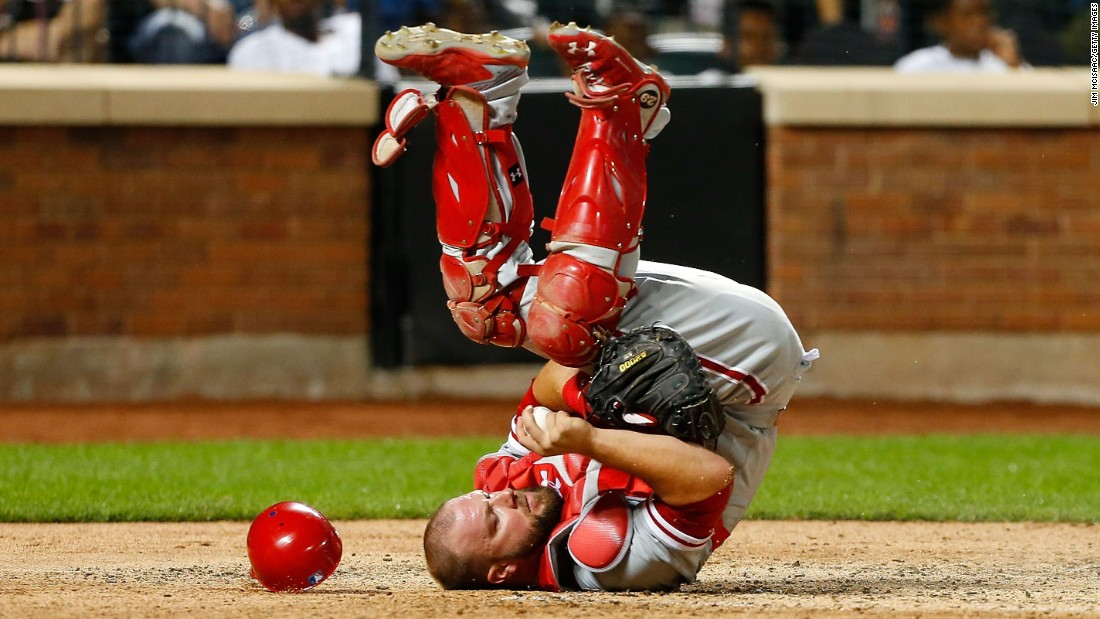 Philadelphia catcher Cameron Rupp holds onto the ball after a home-plate collision Friday, August 26, at New York's Citi Field.