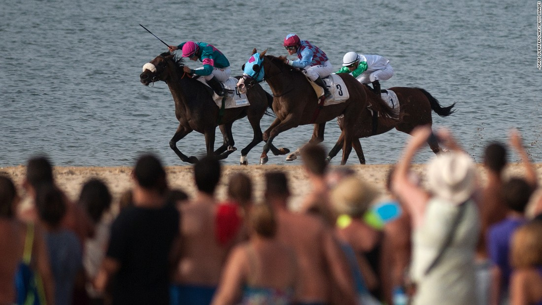 People watch the annual beach horse race at Sanlucar de Barrameda, Spain, on Saturday, August 27.