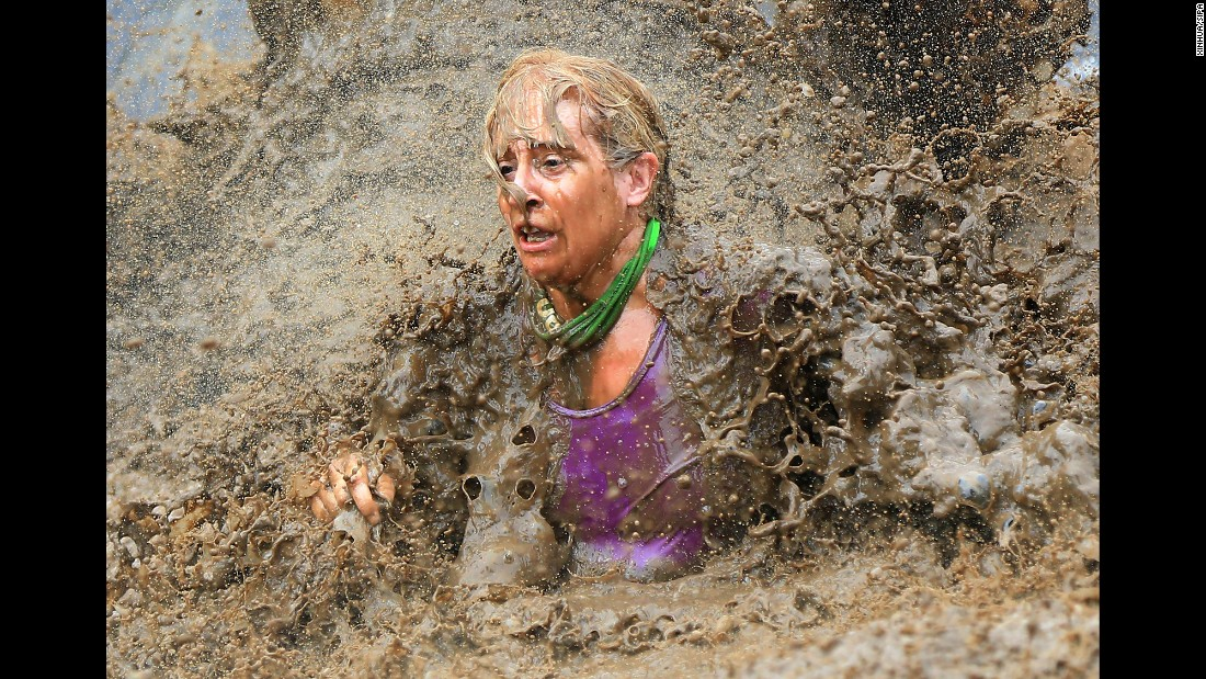 A participant splashes in the mud during the Mud Hero race in Toronto on Sunday, August 28.