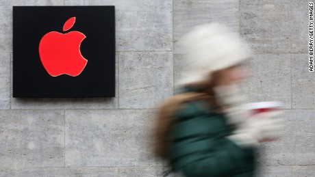 A pedestrian passes a red Apple logo at the Apple Store on December 1, 2014 in Berlin, Germany.