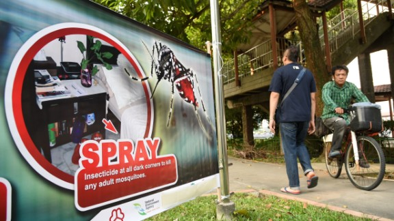Residents are seen walking past a public service announcement banner against the spread of Aedes mosquitoes, a carrier for the Zika virus, at a residential block at Aljunied Crescent neighbourhood in Singapore on August 29, 2016.