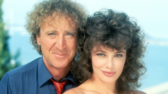 """Wilder poses with actress Kelly LeBrock for a photo promoting the 1984 film """"The Woman in Red."""" Wilder also directed."""