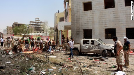 Fighters loyal to the government at the site of a suicide car bombing in Aden.