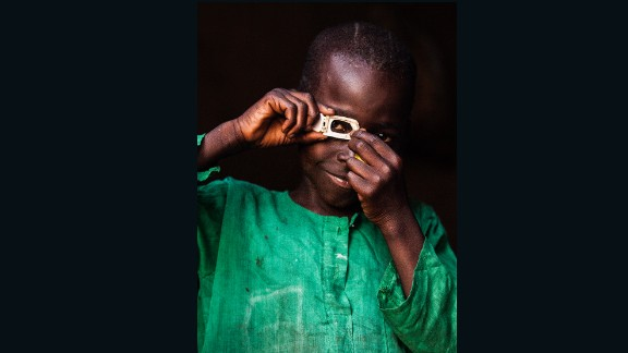 Mustafa (photographer) Central African Republic.  Mustafa poses dressed up as how he sees himself in the future, as a photographer, Central African Republic