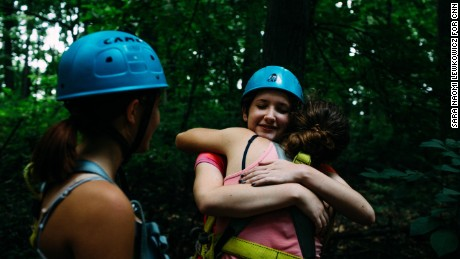 Zoe Jacobs is embraced by a teammate after climbing to the top of a tall log with a rotating platform at the top.