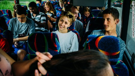 Campers and counselors ride a bus headed for Outward Bound, where they will participate in trust-building exercises.