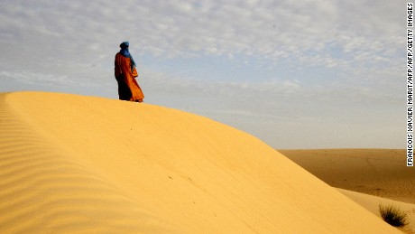 A lone Tuareg man standing on a dune in the desert near Timbuktu, northern Mali, 2005. Jubber visited the ancient city in the aftermath of the 2012 occupation and heard stories from residents who chose to remain.