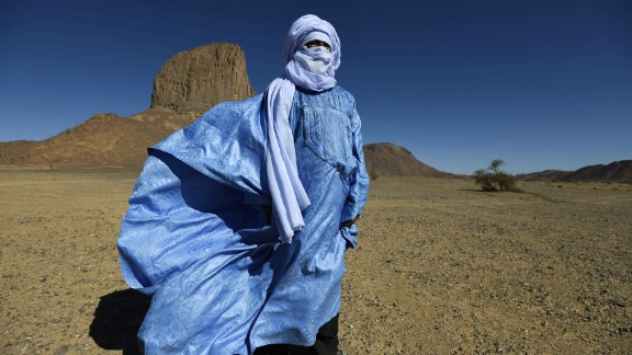 """Tuaregs are the only tribal communities in which men wear veils instead of women. The tangelmust, a wrapped headdress up to eight meters in length, is ubiquitous among the """"blue men of the desert."""" The name does not allude to the muslin headdress, dyed with indigo, but rather because the dye gradually leeches out into the skin of the wearer. Tuaregs use the tangelmust for practical reasons: it protects from the sun and sand, but men will still wear them at night, and even during meals. Men cover their faces with the tangelmust in front of strangers and women, while women are free to show their face."""