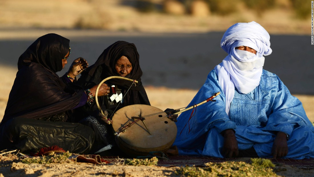 "Tuareg Khoulene Alamine (center), an imzad teacher sits with a poet on the sand of the Tagmart plateau. The imzad, a single-stringed violin played only by Tuareg women, is making a comeback in Algeria. Jubber experienced a wealth of cultures that rubbed off on each other across the Sahara. ""I love not only the richness of the individual cultures,"" he said, ""but the way they intersect with each other in a matrix of interrelatedness."""