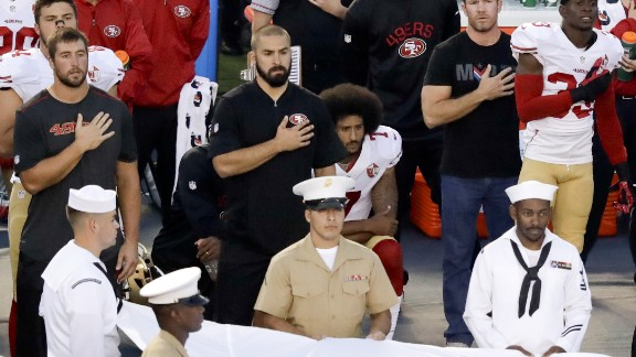 San Francisco 49ers quarterback Colin Kaepernick, middle, sits during the National Anthem before an NFL preseason football game against the San Diego Chargers, Thursday, September 1 in San Diego.