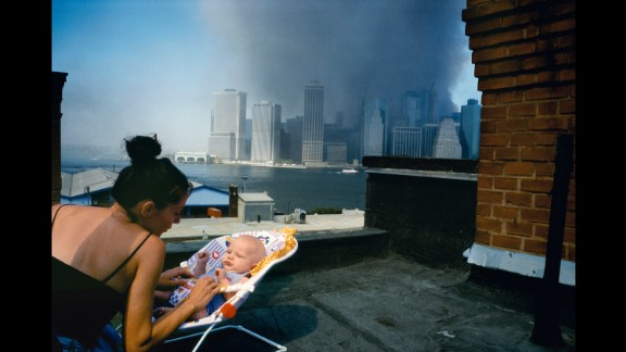 """A mother gently tends to her baby on a Brooklyn rooftop as smoke envelops lower Manhattan. """"There's some sense that, 'Well, this is the world he is coming into,'"""" Alex Webb says."""