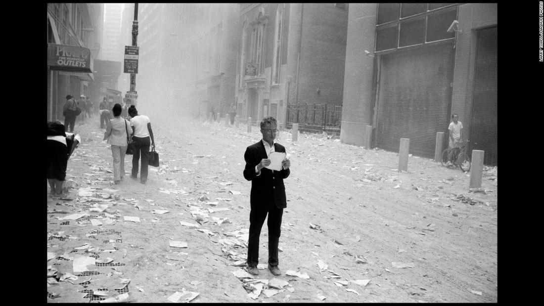 A dazed man picks up a paper that was blown out of the towers in this image by Magnum's Larry Towell.