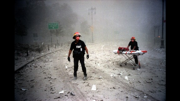 """A pair of masked firefighters near the site of the north tower collapse. """"They were the only ones who stayed,"""" Gilles Peress says of the firefighters and other first responders."""