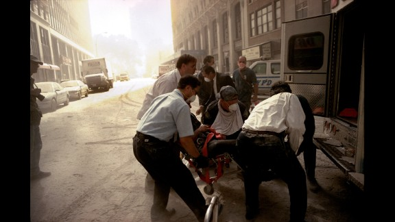 Paramedics lift a victim onto an ambulance for transport to a hospital. (Gilles Peress)
