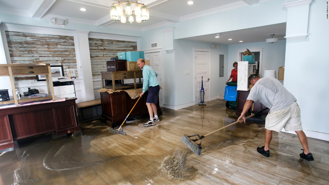 Shawn Stephenson and Marshall Dimick clear water from a real estate office that was flooded by Hermine in Cedar Key, Florida.