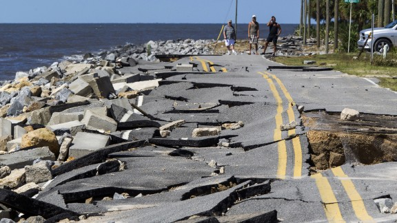 Residents look at an Alligator Point road that collapsed during Hermine's storm surge.