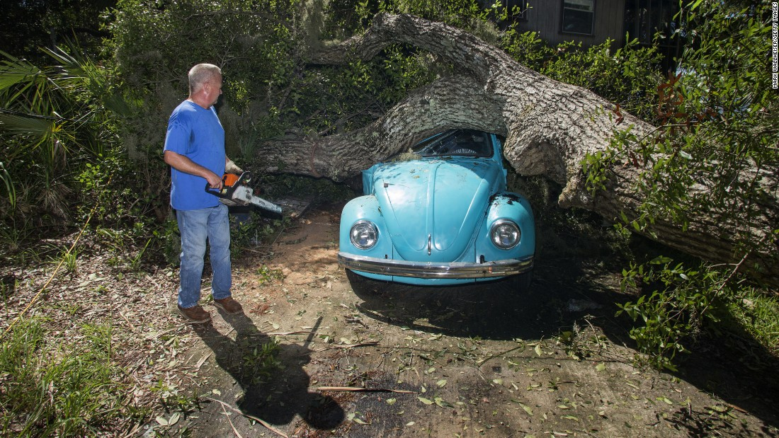 Tom Reams looks at a tree that fell on his house and his daughter's car in Alligator Point, Florida.