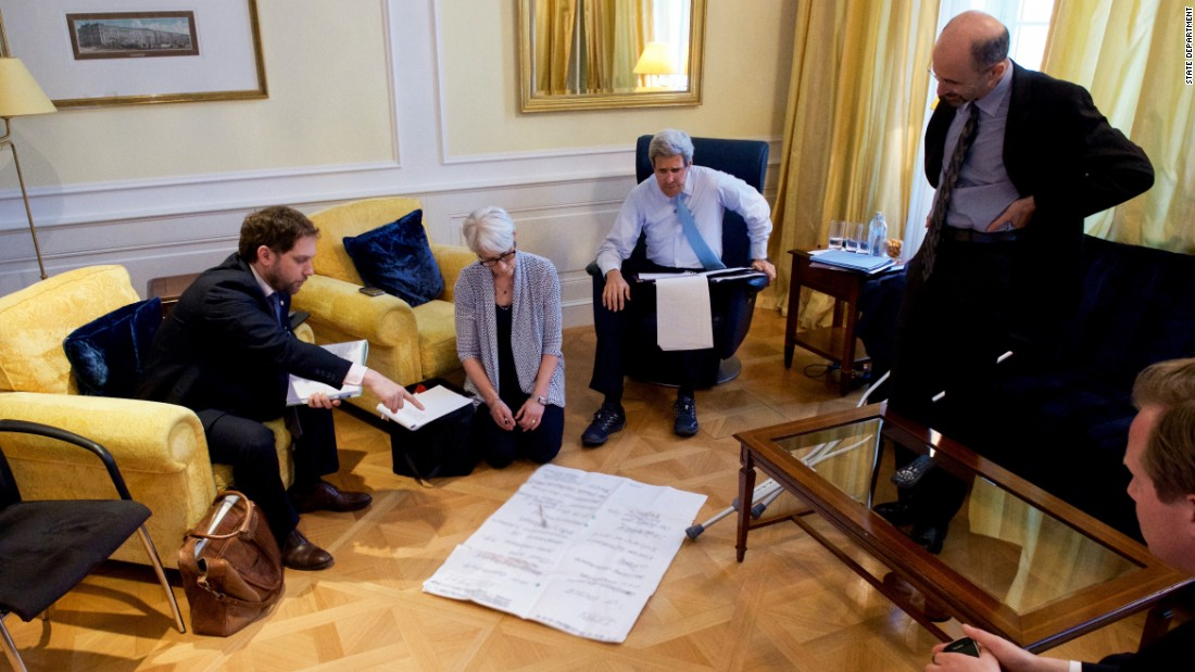 Kerry talks with his staff in 2015 in Paris.