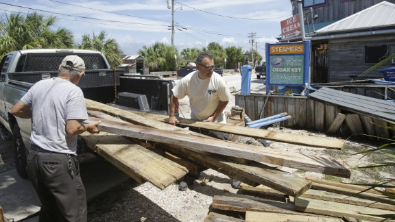 Gus Soldatos and his father, Nick, unload lumber to make repairs on their building September 3, after Hurricane Hermine passed through Cedar Key, Florida.