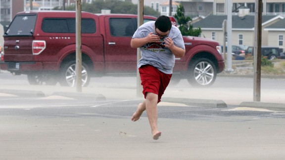 Eli White covers his face from the blowing sand in Nags Head, North Carolina, Saturday, September 3, as the tail of Tropical Storm Hermine passes the Outer Banks. Hermine hit Florida