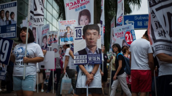 TOPSHOT - A campaigner (C) stands behind a placard of Baggio Leung, 30, one of three candidates from new party Youngspiration, during the Legislative Council election in Hong Kong on September 4, 2016. Young Hong Kong independence activists calling for a complete break from China stood in major elections for the first time on September 4, the biggest vote since 2014 pro-democracy rallies.  / AFP / Anthony WALLACE        (Photo credit should read ANTHONY WALLACE/AFP/Getty Images)