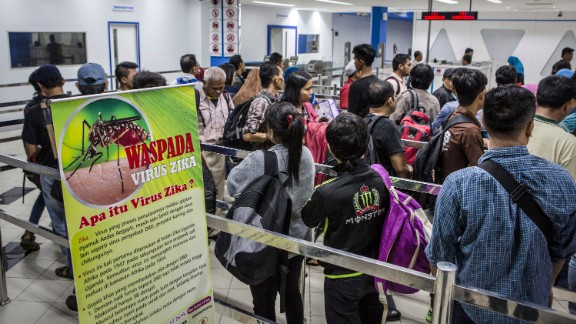A banner about Zika virus is seen as ferry passengers arriving from Singapore get in line at the immigration check on September 4, in Batam, Indonesia.