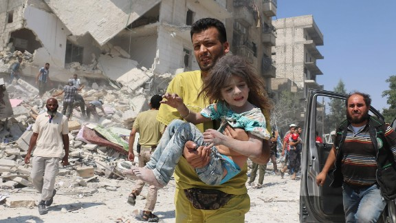 A Syrian man carries a wounded child in eastern Aleppo on August 27, 2016.
