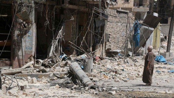 A resident of the Tariq al-Bab neighbourhood of Aleppo looks at damage caused by reported air raids.
