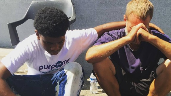 LaRon Tunstill comforts a man after giving him his new shoes.