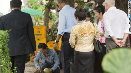US President Barack Obama watches as a woman opens a coconut for him to drink as he makes a surprise stop for a drink alongside the Mekong River in Luang Prabang on September 7, 2016.